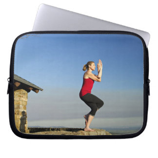 young woman practices yoga on a bluff in the laptop sleeves