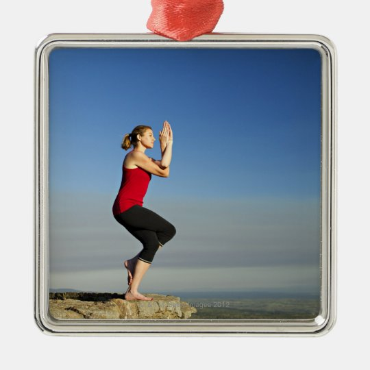 young woman practices yoga on a bluff in the metal ornament