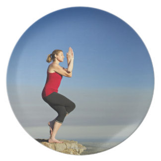 young woman practices yoga on a bluff in the party plates