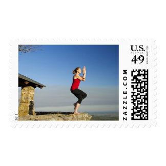 young woman practices yoga on a bluff in the postage stamp