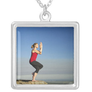 young woman practices yoga on a bluff in the silver plated necklace