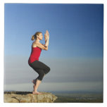 young woman practices yoga on a bluff in the ceramic tiles