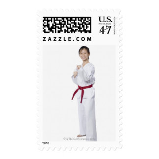 Young woman practicing karate and smiling postage stamp