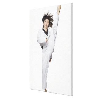Young woman practicing kicking canvas print