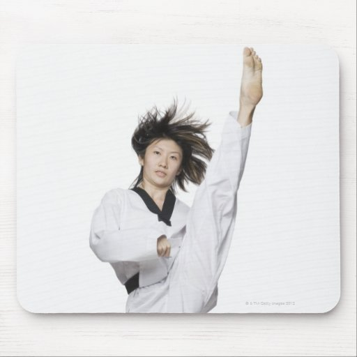 Young woman practicing kicking mouse pad