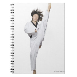 Young woman practicing kicking spiral notebook