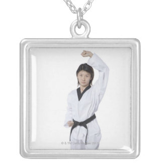 Young woman practicing upper block square pendant necklace