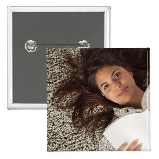 Young woman reading a book lying down button