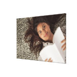 Young woman reading a book lying down gallery wrapped canvas