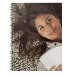 Young woman reading a book lying down notebooks