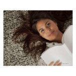 Young woman reading a book lying down poster