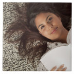Young woman reading a book lying down tile