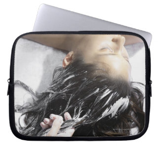Young woman receiving hair treatment laptop sleeve