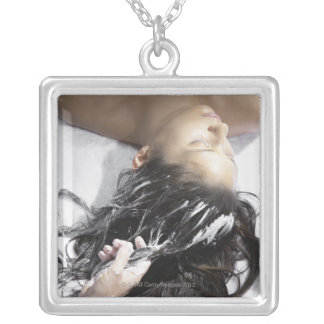 Young woman receiving hair treatment square pendant necklace