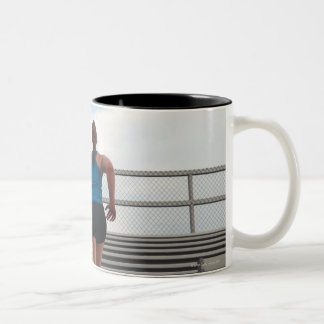young woman running up steps coffee mug