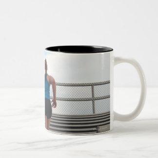young woman running up steps coffee mug