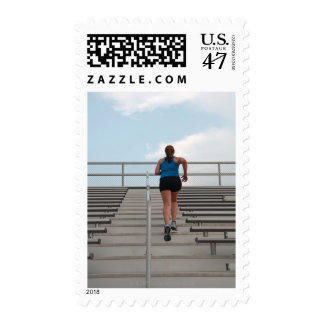 young woman running up steps postage stamp
