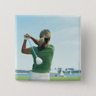 Young woman swinging golf club, rear view button
