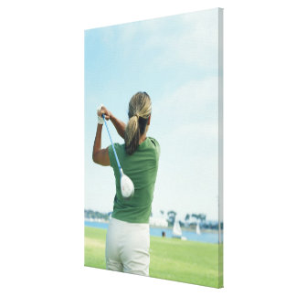 Young woman swinging golf club, rear view canvas print