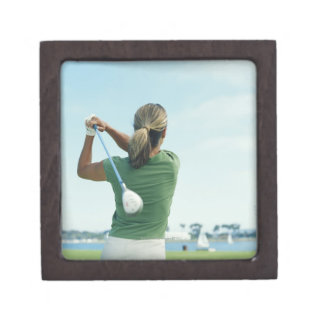 Young woman swinging golf club, rear view gift box
