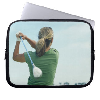 Young woman swinging golf club, rear view laptop sleeve