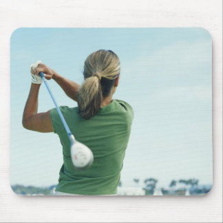 Young woman swinging golf club, rear view mouse pad
