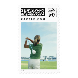Young woman swinging golf club, rear view postage