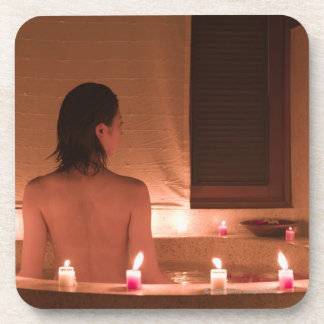 Young woman taking bath with flower petals beverage coaster