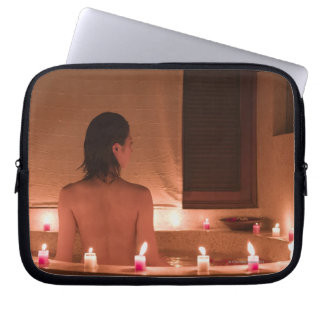 Young woman taking bath with flower petals laptop computer sleeves