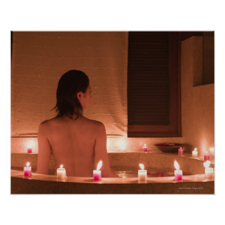 Young woman taking bath with flower petals poster