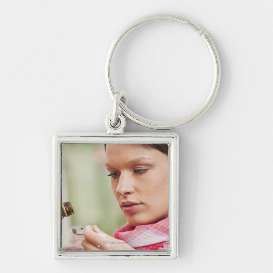 Young woman taking cough medicine keychain