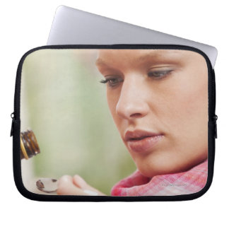 Young woman taking cough medicine laptop sleeve