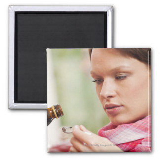 Young woman taking cough medicine magnets