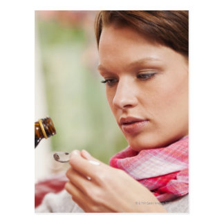 Young woman taking cough medicine postcard