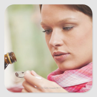 Young woman taking cough medicine square stickers