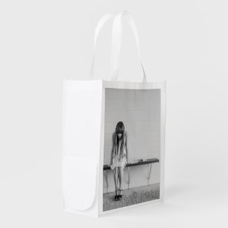 Young woman thinking reusable grocery bags