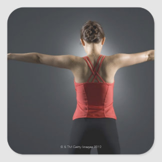 Young woman using dumbbells, rear view, studio square sticker