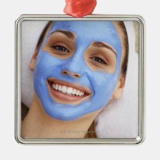 Young woman wearing facial mask, smiling, metal ornament
