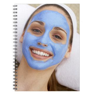 Young woman wearing facial mask, smiling, notebook