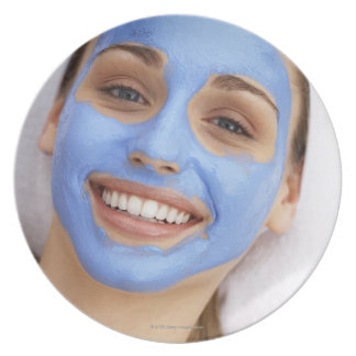 Young woman wearing facial mask, smiling, party plate