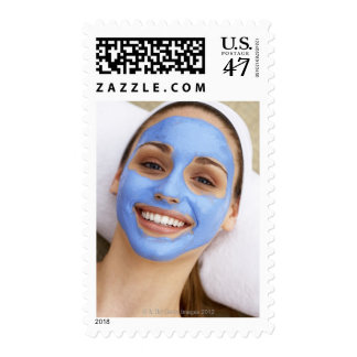 Young woman wearing facial mask, smiling, postage