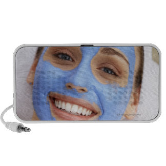 Young woman wearing facial mask, smiling, speaker system