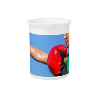 Young woman wearing red boxing gloves blue sky pitcher