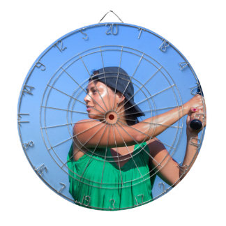 Young woman with baseball bat and cap dart board