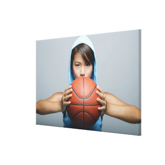 Young woman with basketball looking at camera canvas print