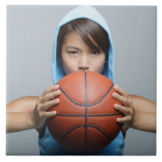 Young woman with basketball looking at camera ceramic tile