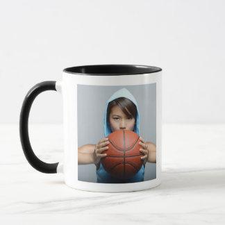 Young woman with basketball looking at camera mug