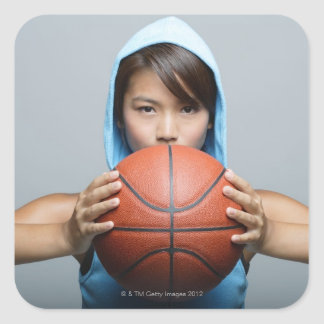 Young woman with basketball looking at camera square sticker