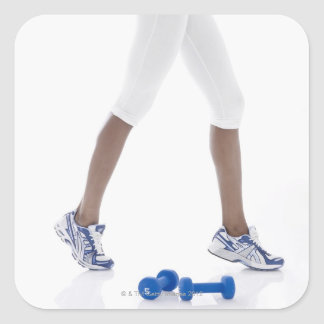 Young woman with dumbbells stretching (low square sticker