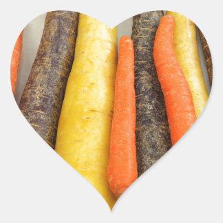 Zanahorias amarillas y anaranjadas púrpuras crudas pegatina en forma de corazón